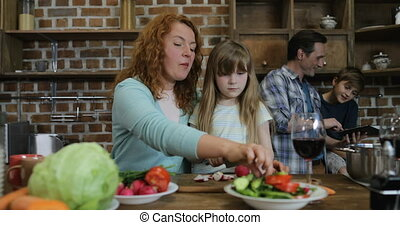 Mother And Daughter Chopping Vegetables While Father With Son Using Tablet Computer, Happy Family Cooking Together In Fitchen At Home