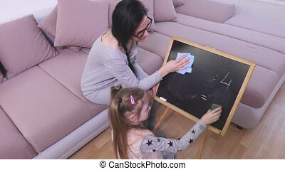 Mother and daughter clean blackboard