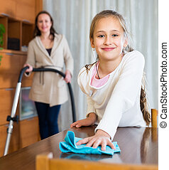 Mother and daughter clean house - Mother is vacuuming and ...