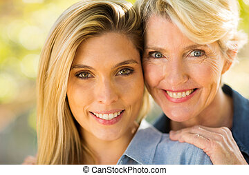 mother and daughter close up - close up portrait of happy...