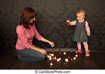 Mother and daughter consider Christmas decorations. Red and...