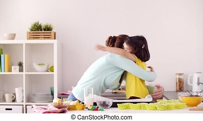 mother and daughter cooking and hugging at home - family,...