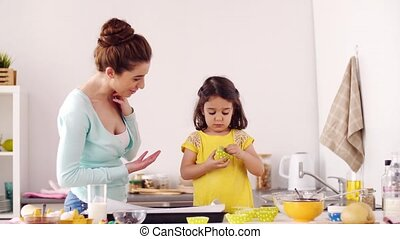 mother and daughter cooking cupcakes at home - family,...