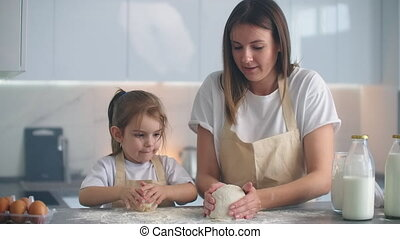 Mother and daughter cooking with dough mold in kitchen. ...