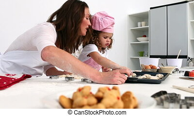 Mother and daughter counting the number of biscuits they...