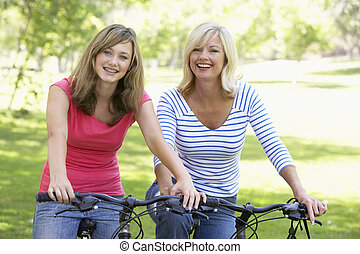 Mother And Daughter Cycling Through A Park