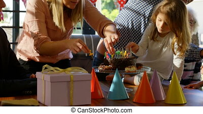 Mother and daughter decorating candles on birthday cake in ...