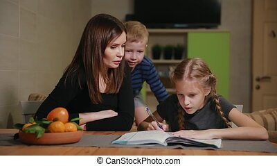 Mother and daughter doing a school homework assignment, a little boy watches it. Brother helps to do homework