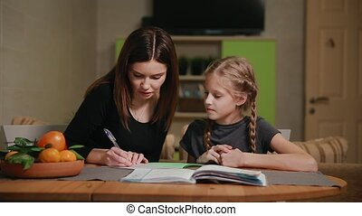 Mother and daughter doing a school homework assignment. Mom...