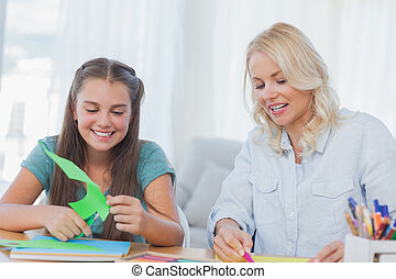 Mother and daughter doing arts and crafts together at home...