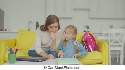 Puzzled mother having difficulties of helping little daughter with complicated schoolwork and looking for answer online with laptop while sitting on sofa and learning together in domestic room.