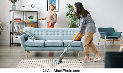 Mature mother and teenage daughter are doing housework cleaning house vacuuming floor and talking together. Household and family lifestyle concept.