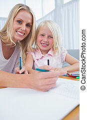 Mother and daughter drawing at table