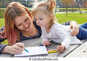 Mother and daughter drawing colors in a park