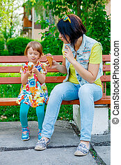 mother and daughter eating ice cream. Mom and daughter enjoy fun ice cream sitting on the bench on summer vacation