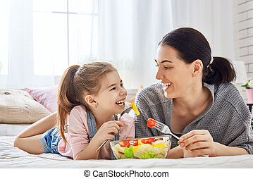 Mother and daughter eating salad - Happy loving family....