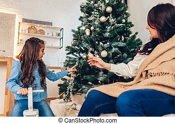 Mother and daughter enjoy Christmas tree at home. Merry Christmas and Happy New Year. Girl riding on rocking horse