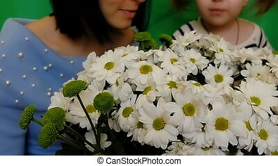 Mother and daughter enjoy the aroma of chamomile. A woman and a child are holding a bouquet of beautiful white flowers. Love and happiness