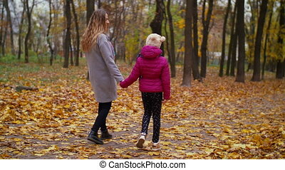 Mother and daughter enjoying colorful autumn nature -...