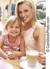 Mother And Daughter Enjoying Cup Of Coffee And Piece Of Cake In Caf?