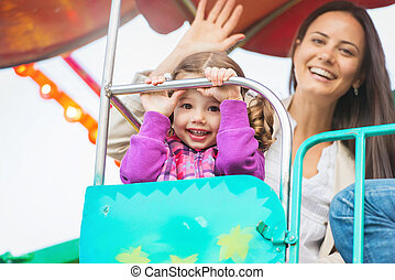 Mother and daughter enjoying fun fair ride, amusement park -...
