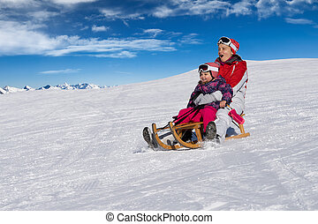 Mother And Daughter Enjoying Sledge Ride In Winter Park