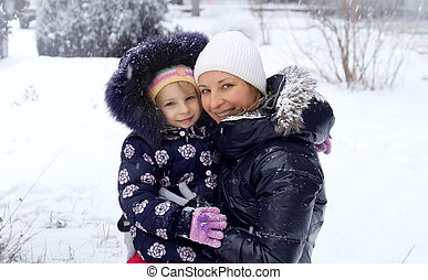 Mother and daughter enjoying snow in winter
