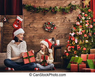 Mother and daughter exchanging gifts - Merry Christmas and...