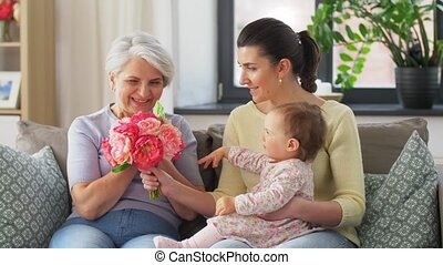 family, generation and celebration concept - mother with baby daughter giving grandmother flowers at home