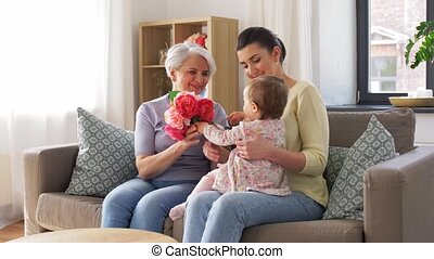 family, generation and greeting concept - mother with baby daughter giving grandmother flowers at home