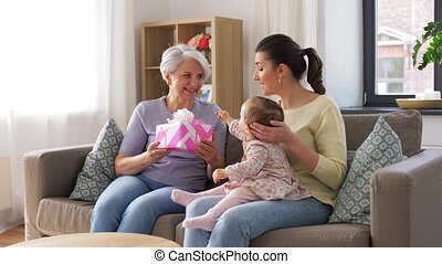 family, generation and greeting concept - mother with baby daughter giving gift box to grandmother at home