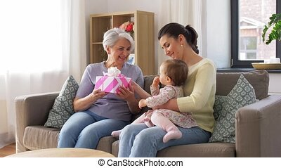 mother and daughter giving grandmother present - family, ...