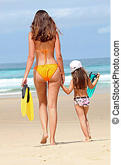 Mother and daughter going swimming in the sea