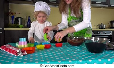 Mother and daughter hands preparing dough for cup-cake on...