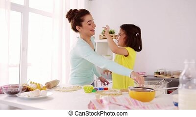 mother and daughter having fun at home kitchen - family,...