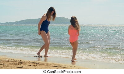 Mother and daughter having fun at the beach 4k