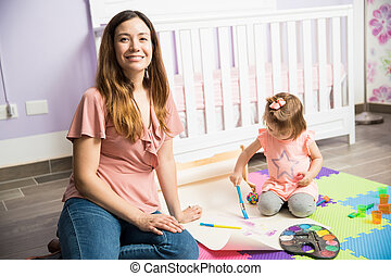 Mother and daughter having fun in the nursery