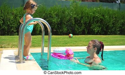 Mother and daughter helping to girl to enter in the pool -...