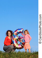 Mother and daughter holding an inflatable figure of six on blue sky, one of which sits on his haunches, and second is in meadow with green grass