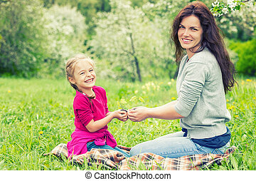 Mother and daughter holding little green plant in hands