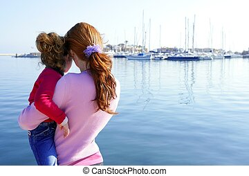 Mother and daughter hug looking blue marina - Mother and...
