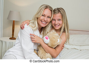 Mother and daughter hugging in bed