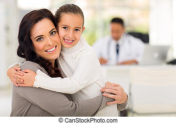 mother and daughter hugging in doctor's office