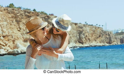 Mother and daughter hugging on beach - Mother and daughter...