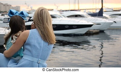 mother and daughter in a blue dress and blue big bow standing on the dock