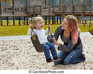 Mother and daughter in a swing at the park - Mother and ...