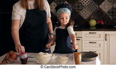 Mother and daughter in aprons prepare cookie dough in the kitchen. Portrait.