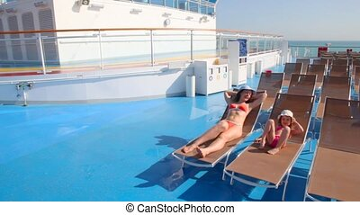mother and daughter in bikini lying on deckchairs - mother...