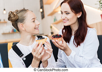 mother and daughter in cafe with desserts