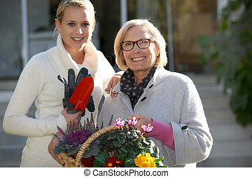 Mother and daughter in garden with flower basket